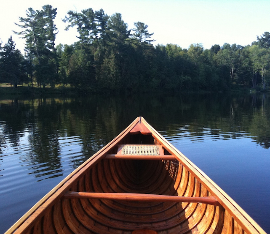 the bow of a wooden canoe on a lake