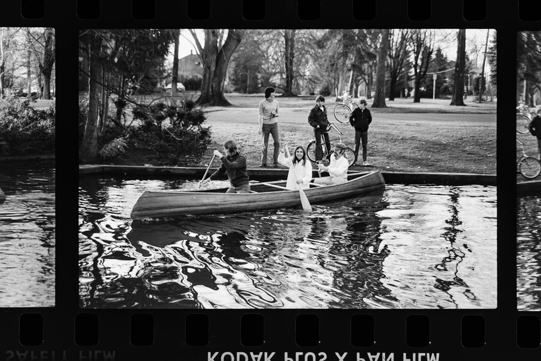 people paddling a canoe in black and white