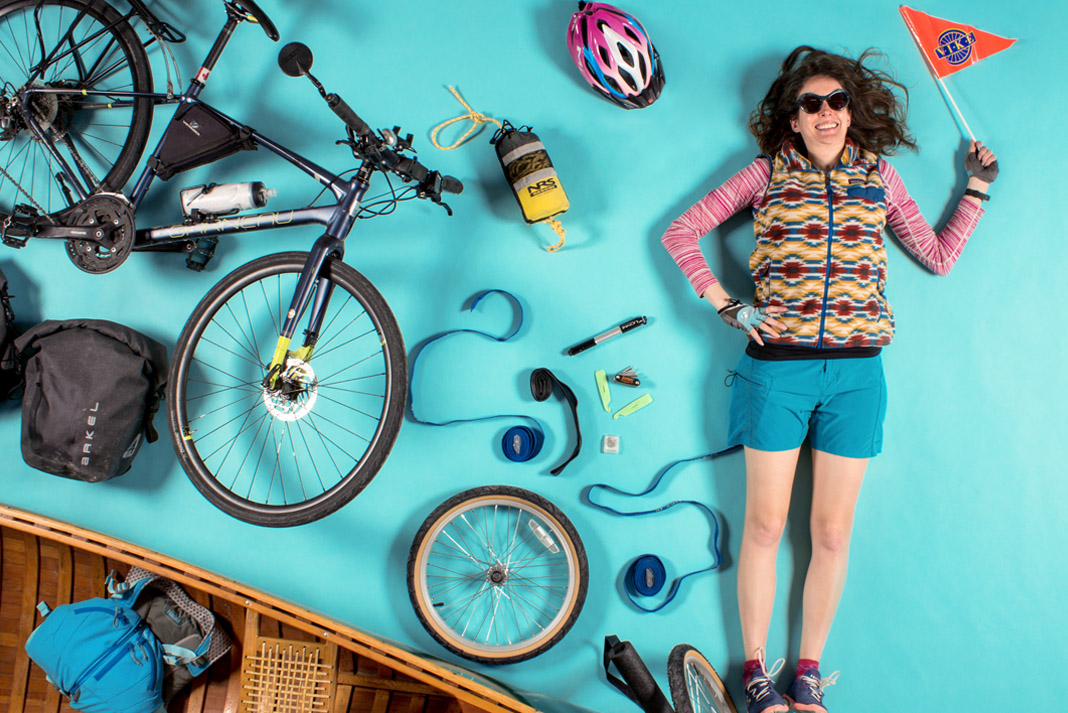 woman surrounded by pack rafting and bike gear