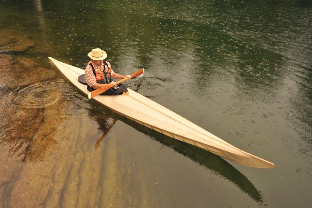 Man paddling a long wooden canoe