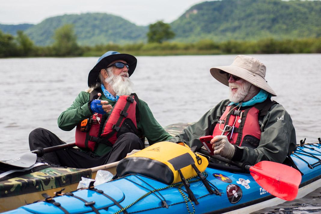 two men in kayaks laughing