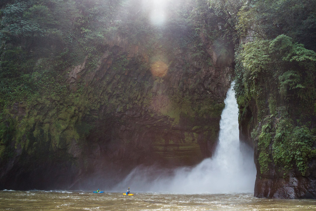 waterfall with kayakers underneath