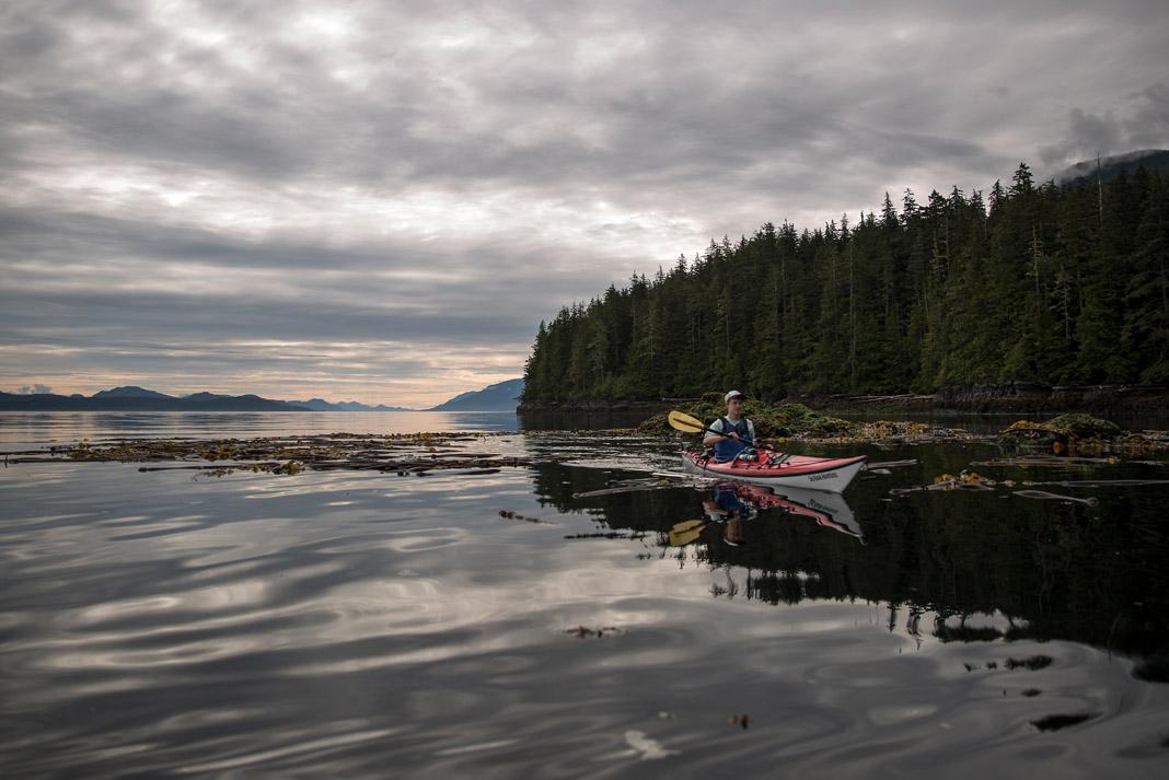 man sea kayaking on lake with scenic background