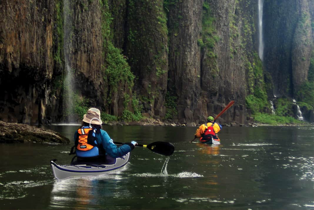 two people paddling past large cliffs with waterfalls