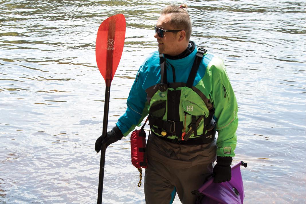 man holding a kayak paddle and wearing paddling gear