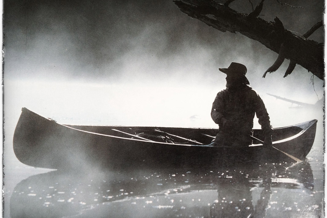 man paddling in a canoe in black and white