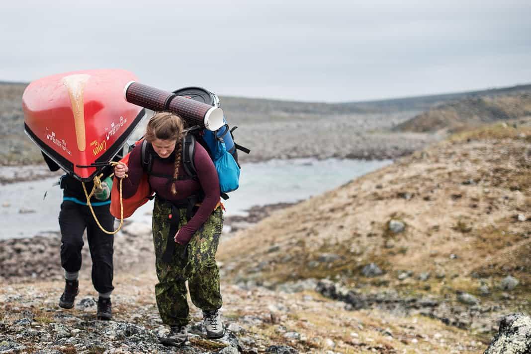 two women portaging heavy canoe