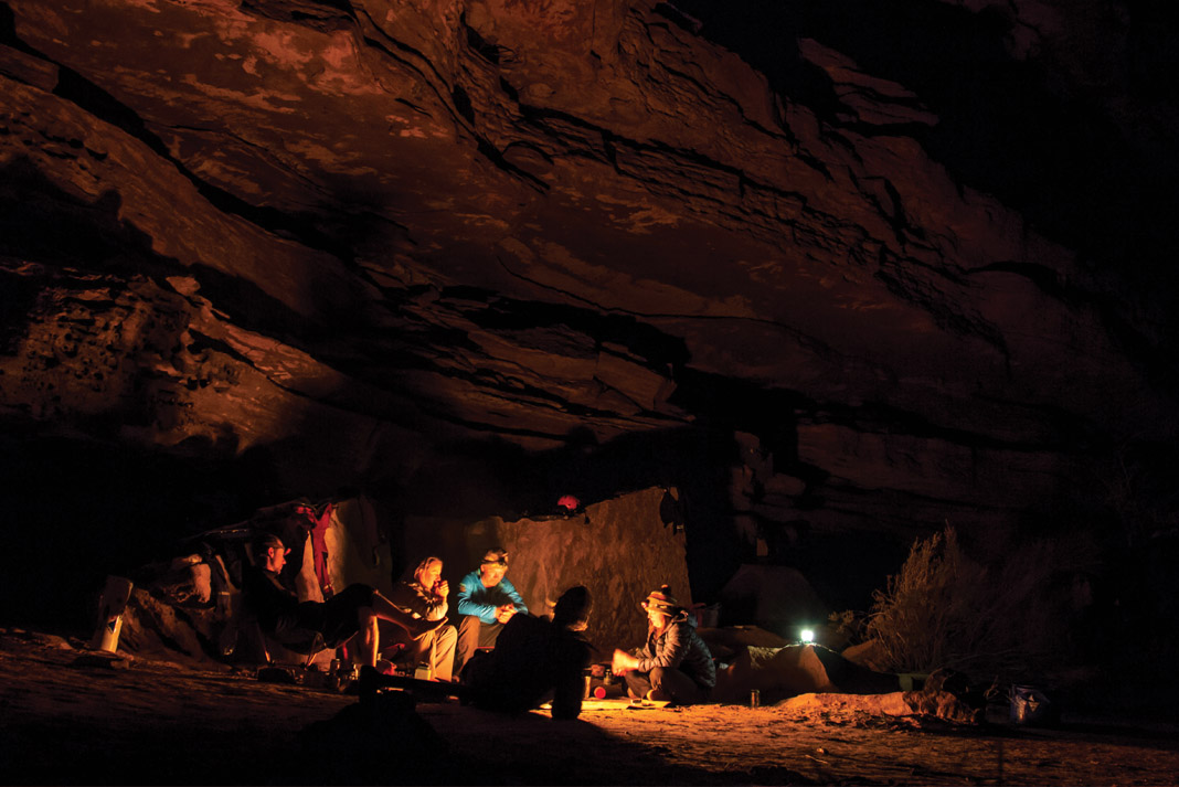 group of people sitting by fire in cave