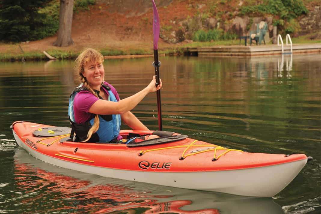 woman paddling a red recreational kayak