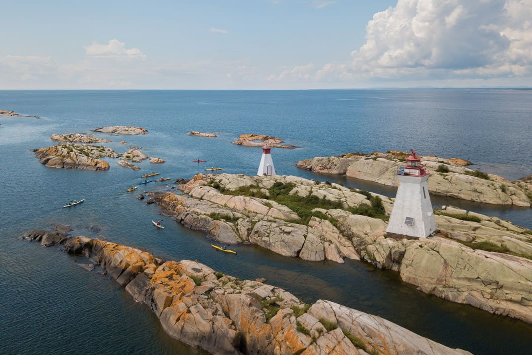 lighthouses on an island surrounded by sea kayaks