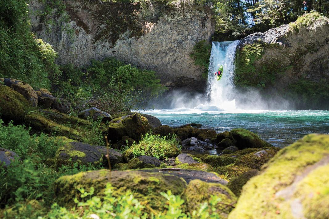 man kayaking off a waterfall