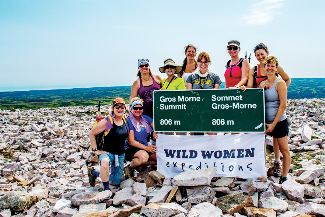 9 women standing in front of a sign
