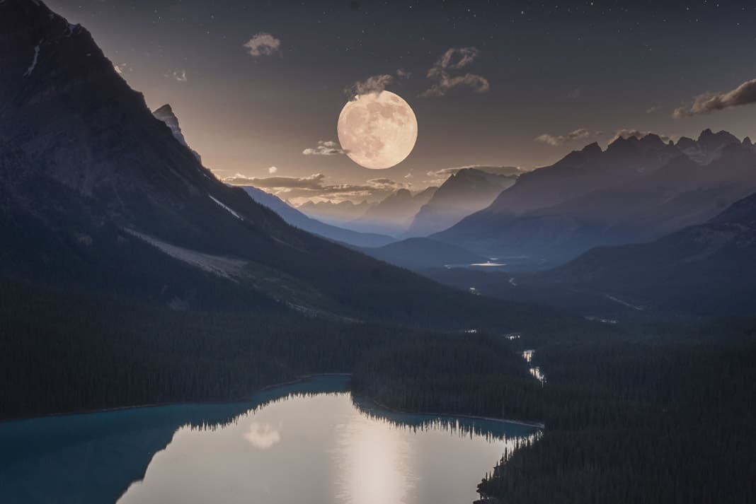 full moon over mountains and a lake
