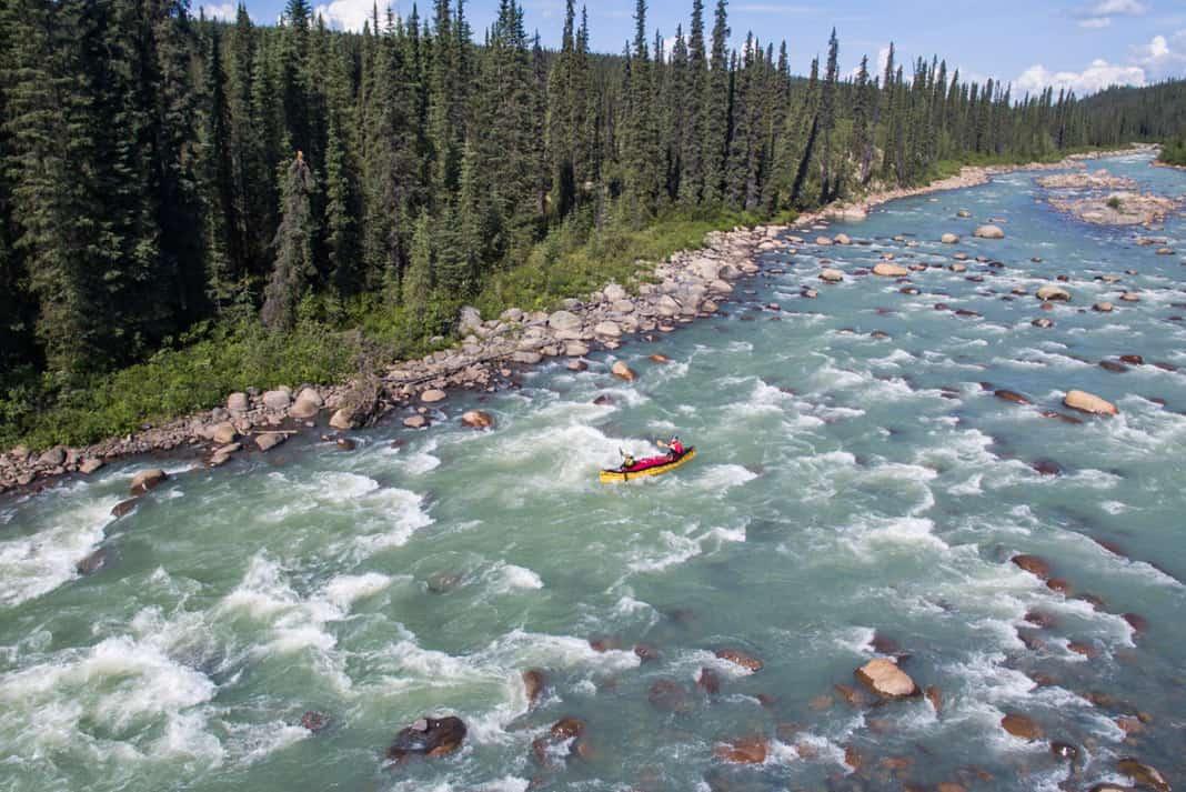 canoe going through rapids