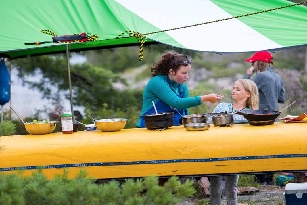 two women eating off a canoe
