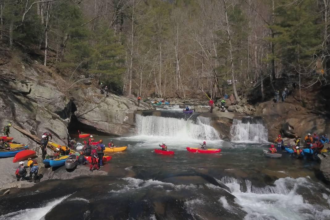 canoes beside a waterfall