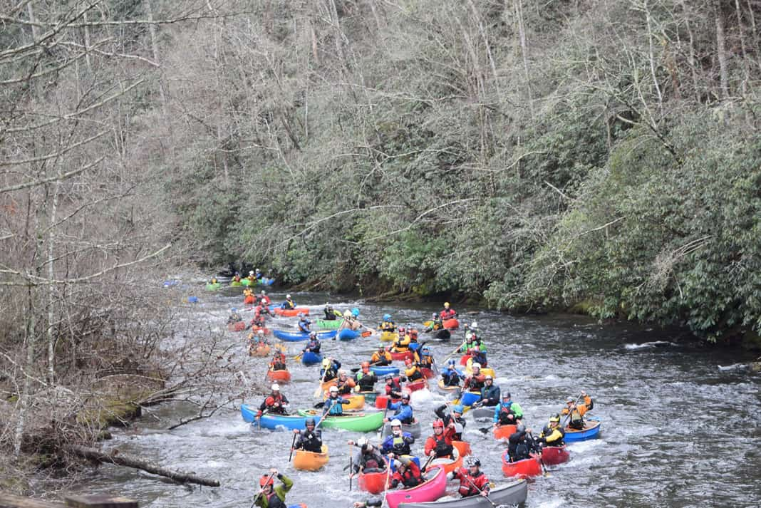several canoeist paddling down a rapid