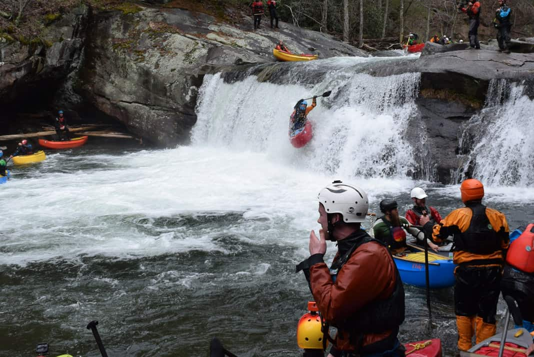 man in a red canoe dropping off a waterfall