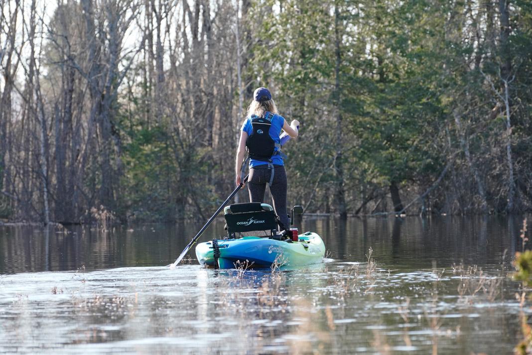 woman standing and paddling the ocean kayak