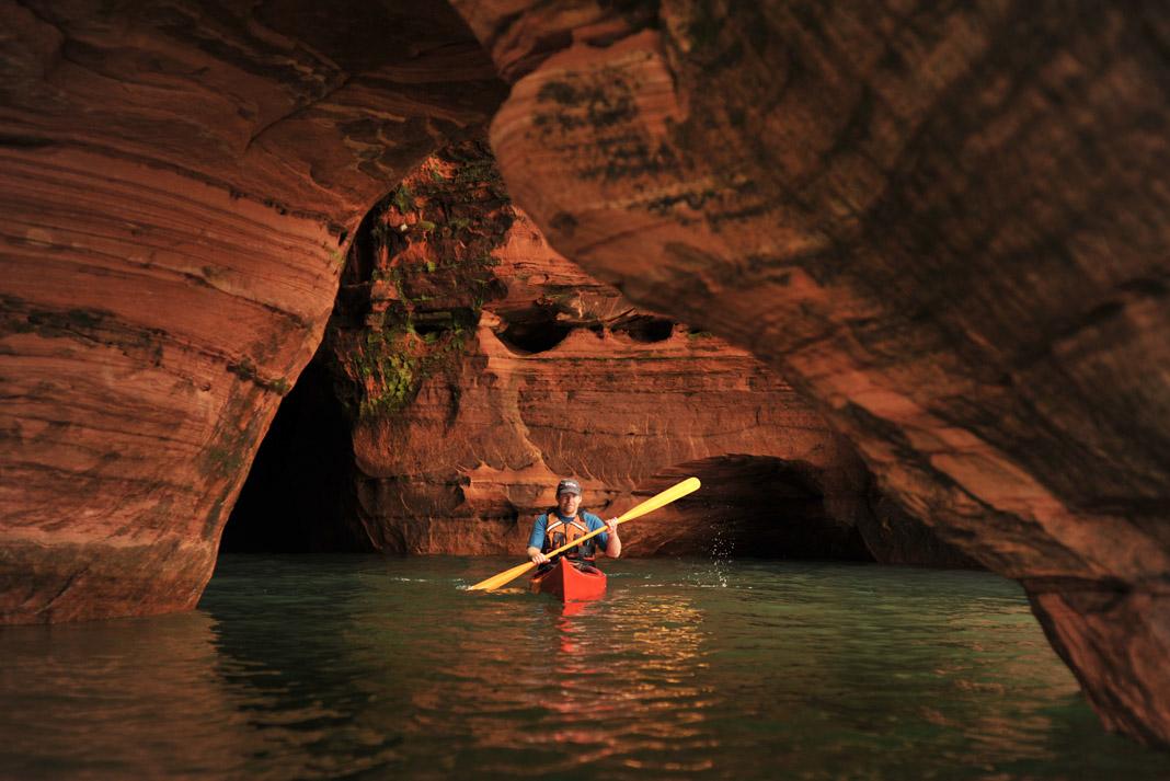 Kayaker paddles through red caves