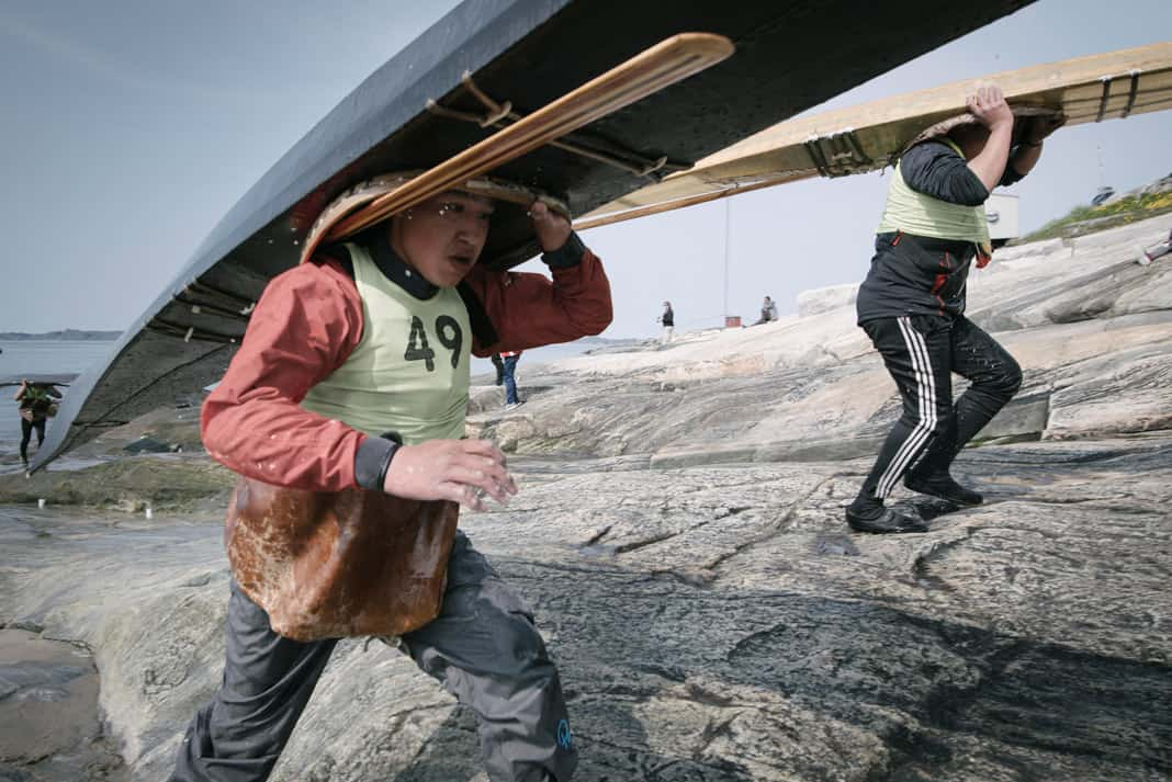 Karl Bjorn Hansen runs with his qajaq up the shoreline in the youth portage race.