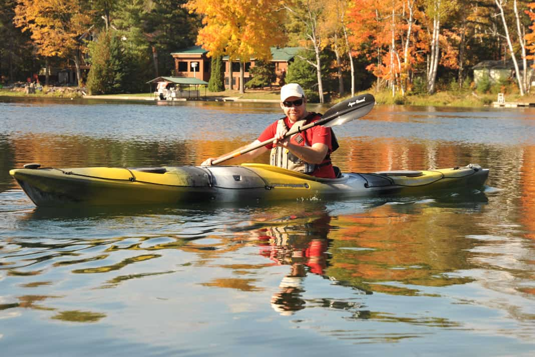 person paddling Wilderness Systems' Tsunami 145 touring kayak on a lake