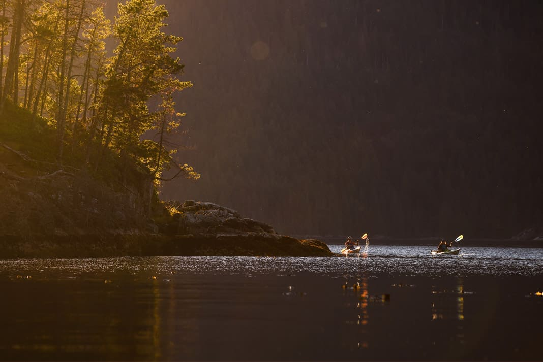 two kayakers coming around the corner of an island on a lake