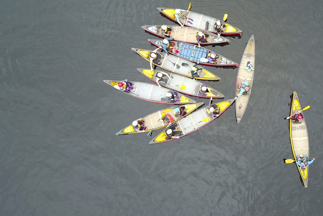 Group of tandem canoeists gather to have a talk