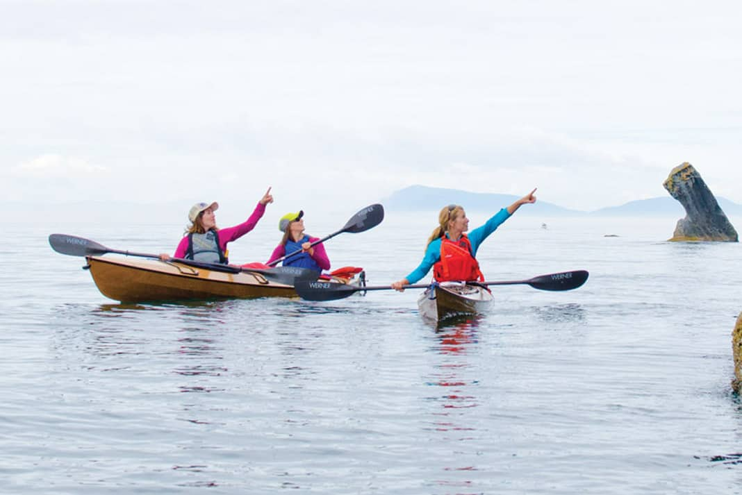 three women paddling touring kayaks and pointing at scenic rocks