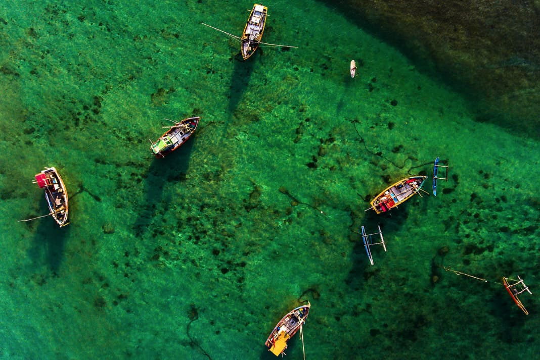 an aerial shot of several fishing boats paddling in Sri Lanka