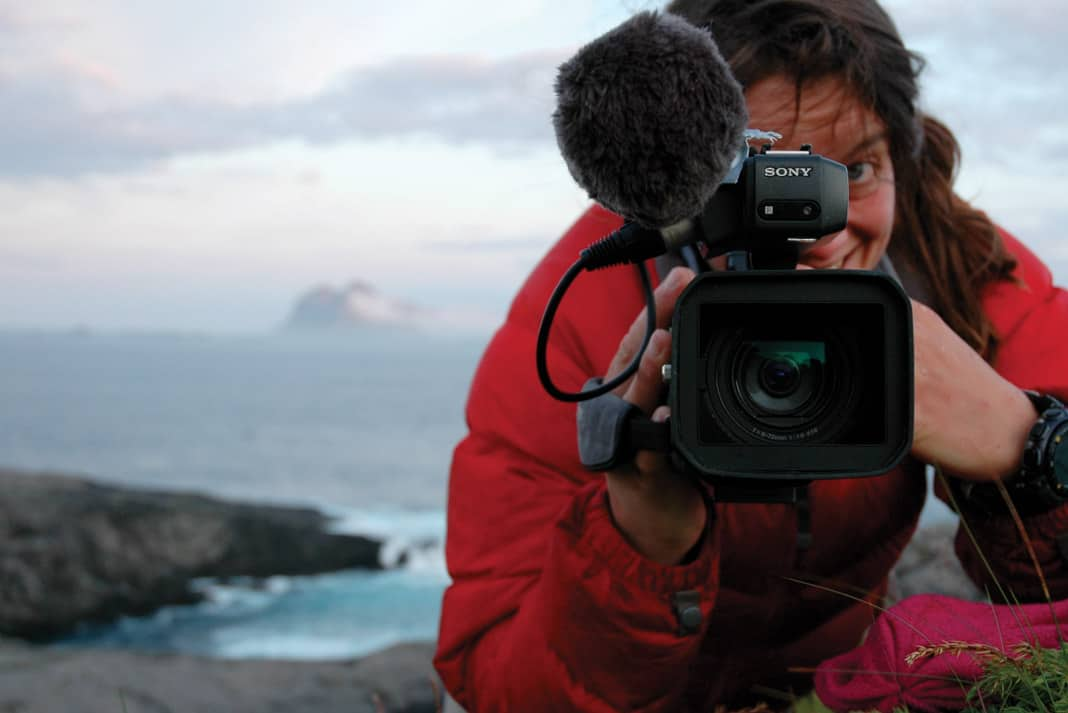 Justine Curgenven holding a video camera and filming