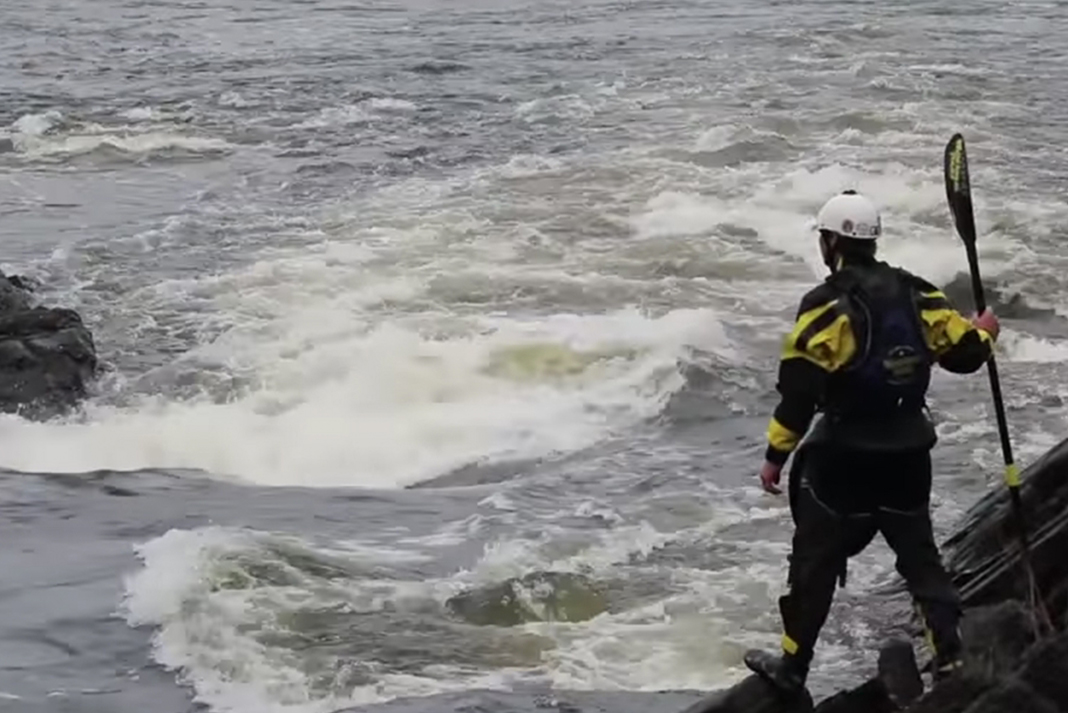Joel Kowalski scouts a set of rapids at the side of the river.