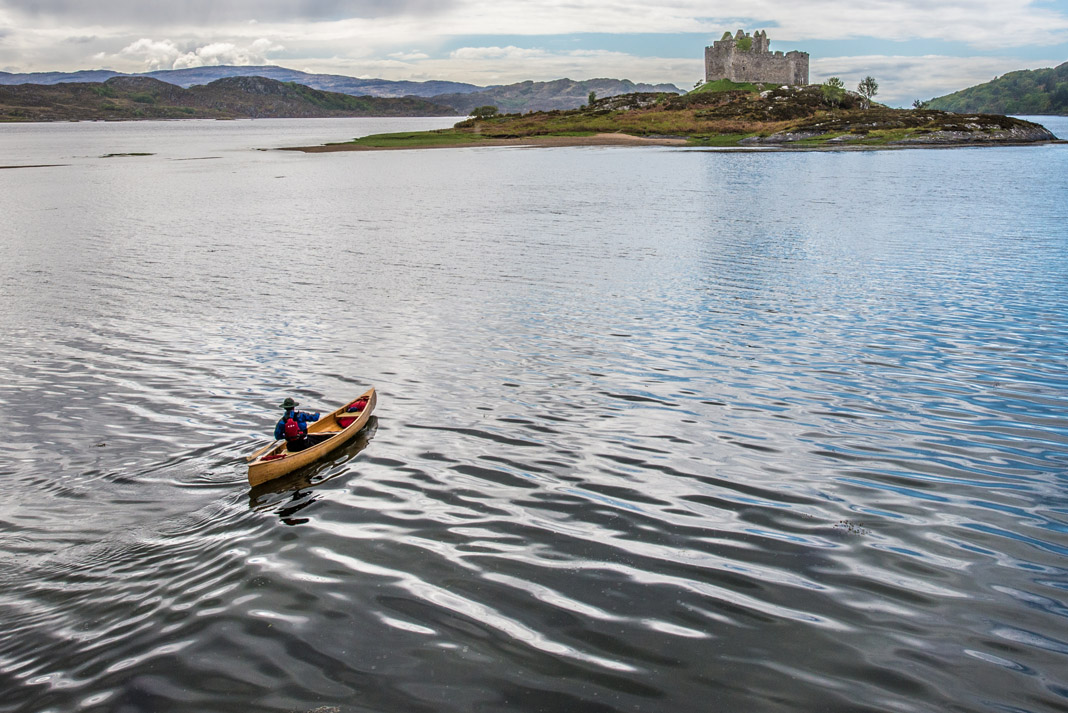 a person paddling a canoe on a lake towards a castle in Scotland, UK.