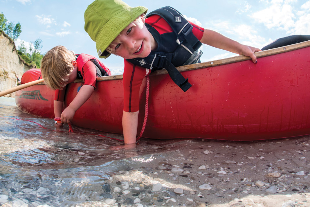 two kids in a canoe that has been beached playing with the water underneath them
