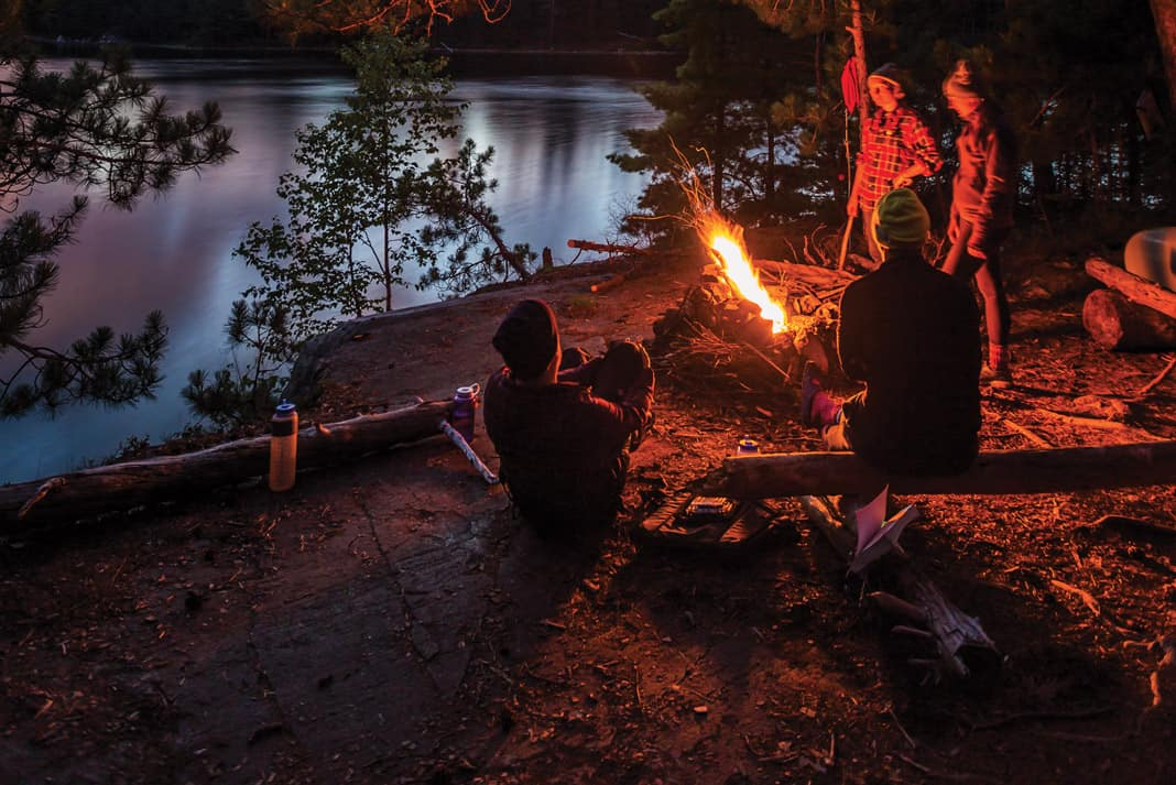 4 people standing by a fire at their canoe trip campsite