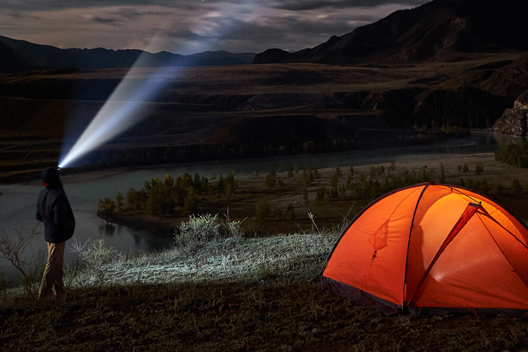 Camper standing next to tent with hat that has LED lights built into it
